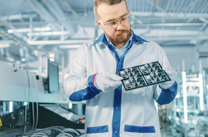 Employee controls the quality of printed circuit boards