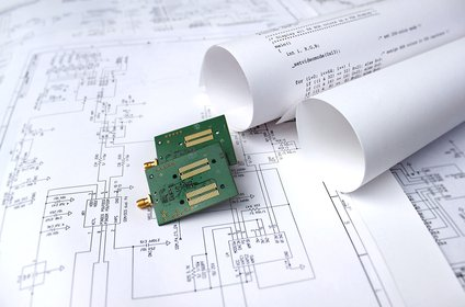 Printed circuit boards lie on printed circuit drawings